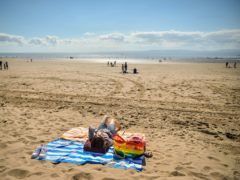 People sunbathing on the beach (PA)