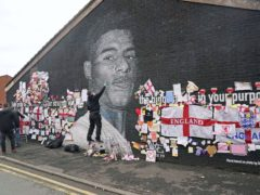 Street artist Akse repairs the mural of Manchester United striker and England player Marcus Rashford (Danny Lawson/PA)