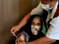 Seventy-six-year-old Kaironesa Sheik Suleman Allie receives a first dose of the Pfizer vaccine (Nardus Engelbrecht/AP)