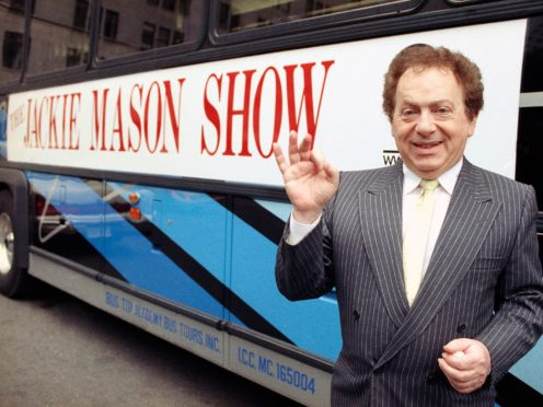 Comedian Jackie Mason stands beside a bus displaying a sign advertising his TV show in 1992 (AP)