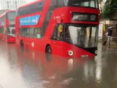 Buses in flood water in Battersea, south London (Hebe Campbell/PA)