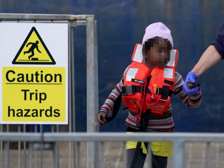 A young girl is escorted by a Border Force officer as a group of people thought to be migrants are brought in to Dover, Kent (PA)