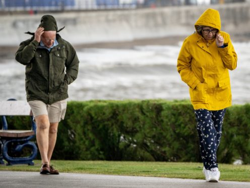 People pull down their hoods to shelter from the wind as they walk along the sea front in Porthcawl, Wales (Ben Birchall/PA)