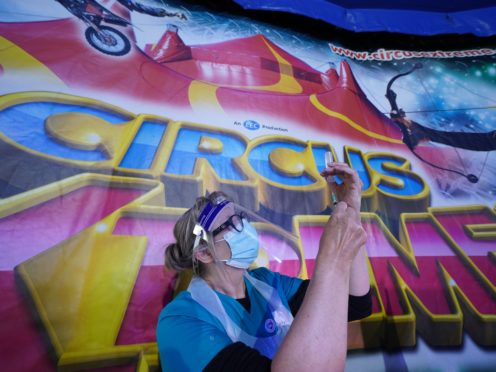 A doctor prepares a syringe at a pop-up Covid-19 vaccination clinic in the marquee of Circus Extreme in Halifax (Owen Humphreys/PA)