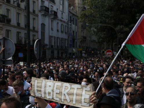 Protesters hold up a banner which reads 'freedom' in French during a demonstration in Paris (Adrienne Surprenant/AP)