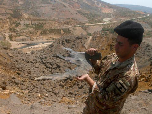 A Lebanese army soldier displays part of an Israeli missile from an air strike in Dimashqiya farmlands, southern Lebanon (Mohammed Zaatari/AP)