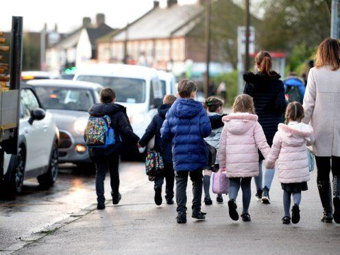 Parents walk their children to school in Hornchurch, Essex (PA)