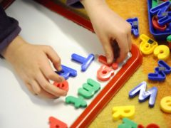 A child playing with letters (Dominic Lipinski/PA)
