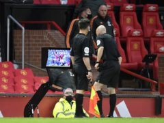 Referee Anthony Taylor consults a monitor before overturning a penalty decision in a Premier League match between Manchester United and Liverpool (Peter Powell/PA)