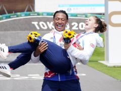 Beth Shriever is held aloft by Kye Whyte after she won BMX racing gold to add to his silver at the Tokyo Olympics (Danny Lawson/PA Images).