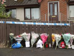 Flowers and soft toys left at the scene in Dungannon, Co Tyrone (PA)