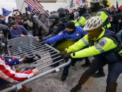 Violent insurrectionists loyal to Donald Trump hold on to a police barrier at the Capitol in Washington on January 6 (AP)