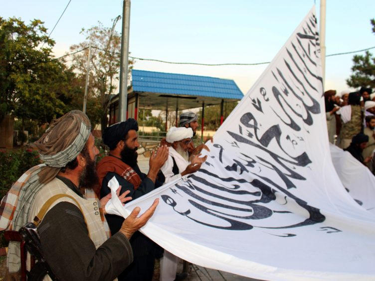 Taliban fighters pray while raising their flag at the provincial governor's house in Ghazni, south-eastern Afghanistan (Gulabuddin Amiri/AP)