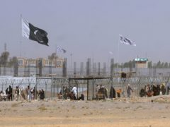 Pakistan and Taliban flags flutter on their respective sides while people walk through a security barrier to cross a border between Pakistan and Afghanistan, in Chaman, Pakistan (Jafar Khan/AP)