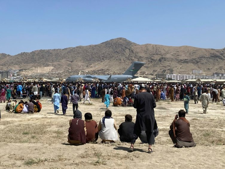 Hundreds of people gather near a plane at the perimeter of the international airport in Kabul, Afghanistan (Shekib Rahmani/AP)