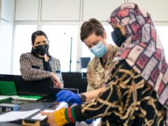 Home Secretary Priti Patel, left, watches as Afghan refugees are processed at Heathrow Airport (Dominic Lipinski/PA)