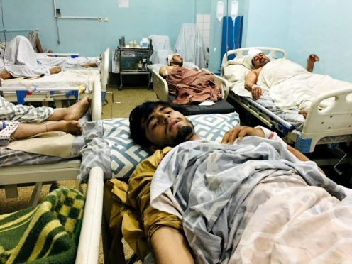 Wounded Afghans lie on a bed at a hospital after a deadly explosions outside the airport in Kabul (AP)