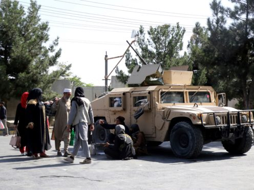 Taliban fighters on guard outside the airport in Kabul (Wali Sabawoon/AP)