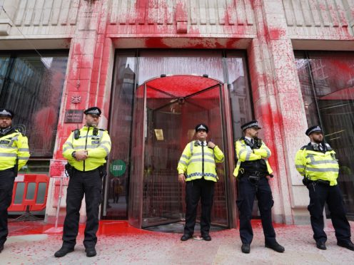 Police officers stand in front of the Guildhall, which has been daubed in paint (Stefan Rousseau/PA)