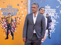 """Taika Waititi, left, a cast member in """"The Suicide Squad,"""" is joined by his date, singer Rita Ora, as he poses at the premiere of the film at the Regency Village Theatre, Monday, Aug. 2, 2021, in Los Angeles. (AP Photo/Chris Pizzello)"""