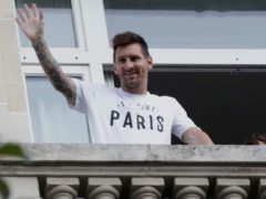 Lionel Messi, who has completed his move to Paris St Germain, waves to supporters from his hotel balcony (Adrienne Surprenant/AP).