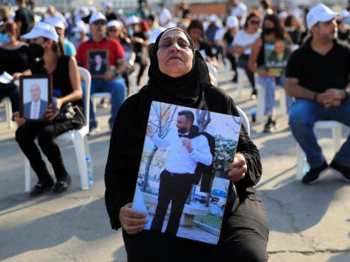 A woman holds a picture of her son, who was killed in the massive blast last year at the Beirut port (Hussein Malla/AP)