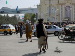 Taliban fighters stand guard in front of the Hamid Karzai International Airport, where thousands gathered on Sunday night and Monday morning (Rahmat Gul/AP)
