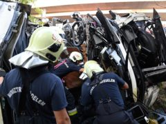 Firefighters check out the wrecked bus which flipped over and crashed (Zoltan Mihadak/MTI via AP)