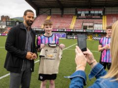 Rio Ferdinand with a fan during the BT Hope United match at at Crusaders FC's Seaview ground in Belfast on the eve of the Super Cup to raise awareness about the devastating impact of online hate in sport and among young people (Liam McBurney/PA)