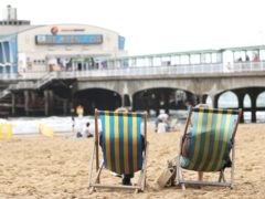 People relax on deckchairs (PA)