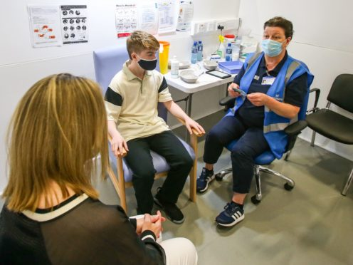 Kevin Mckeon, 14, receives his first dose of the Covid-19 vaccine in Dublin (PA)