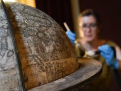 National Trust conservator Samantha Taylor cleans the rare Elizabethan globe (Andrew Matthews/PA)