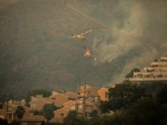 A helicopter makes a water drop over a wildfire in Estepona, Spain (AP Photo/Sergio Rodrigo)
