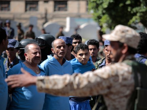 Police troopers stand guard next to men convicted of involvement in the killing of a senior Houthi official Saleh al-Samad before their execution at Tahrir Square in Sanaa (AP)