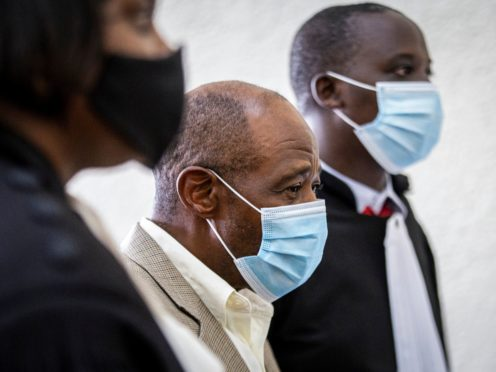 """FILE – In this Monday, Sept. 14, 2020 file photo, Paul Rusesabagina, center, whose story inspired the film """"Hotel Rwanda"""" for saving people from genocide, appears at the Kicukiro Primary Court in the capital Kigali, Rwanda. A court in Rwanda said Monday, Sept. 20, 2021 that Rusesabagina, who boycotted the announcement after declaring he didn't expect justice in a trial he called a """"sham"""", is guilty of terror-related offenses. (AP Photo, File)"""