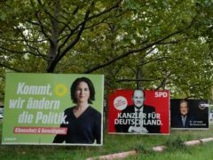 Election campaign billboards of candidates for chancellery Annalena Baerbock, Olaf Scholz and Armin Laschet displayed in central Berlin (Markus Schreiber/AP)