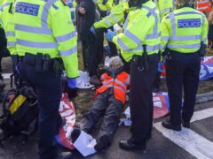 Police officers detain a protester from Insulate Britain occupying a roundabout leading from the M25 motorway to Heathrow Airport in London (Steve Parsons/PA)