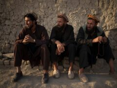 Afghans sit outside a mosque in Kabul on Monday. The Taliban has ordered barbers in one province not to trim or shave beards (Felipe Dana/AP)