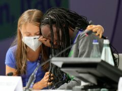 Ugandan climate activist Vanessa Nakate is comforted by Swedish activist Greta Thunberg (AP)
