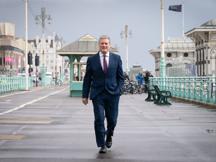 Labour leader Sir Keir Starmer walks along Brighton seafront promenade during the Labour Party conference (Stefan Rousseau/PA)