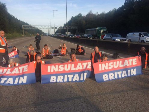 Insulate Britain protesters sit on the motorway on the M25 in Surrey to campaign to improve home insulation (Insulate Britain/PA)