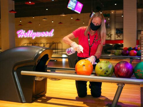 A member of staff at a Hollywood Bowl in Essex cleans the bowling balls (Steve Parsons/PA)