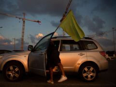A man places a green flag on his car as he prepares to join a convoy of cars and protest against the green pass changes (Oded Balilty/AP)