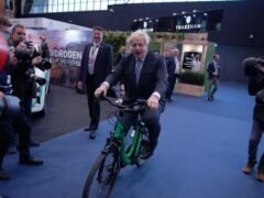 Prime Minister Boris Johnson on a bicycle in the Manchester Central Convention Complex (Peter Byrne/PA)