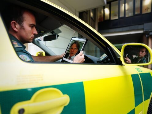 Paramedic Patrick Hunter, from the London Ambulance Service, uses an iPad to talk with consultant neurologist and stroke physician Dr Rob Simister (Victoria Jones/PA)