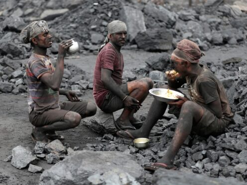 Labourers eat lunch at a coal loading site in the village of Godhar in Jharia (AP)