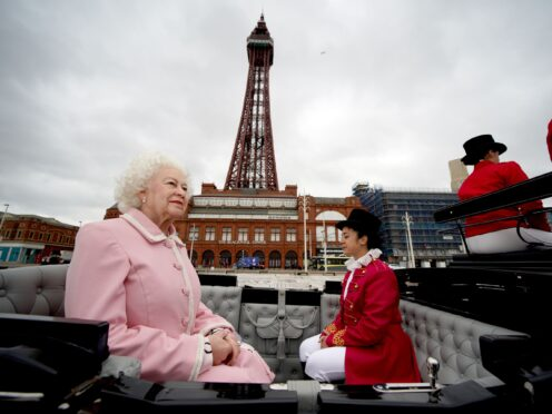 The wax figure of the Queen is driven along Blackpool's seafront in a horse and carriage along the seafront as it makes its way to Madame Tussauds (Peter Byrne/PA)