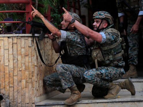 Lebanese security forces react to gunfire during a protest in Beirut (Hussein Malla/AP)
