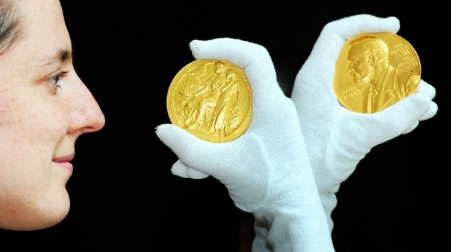 Tacye Phillipson, Senior Curator of Modern Science, examines Sir James Black's Nobel Prize Medal. Copyright National Museums Scotland