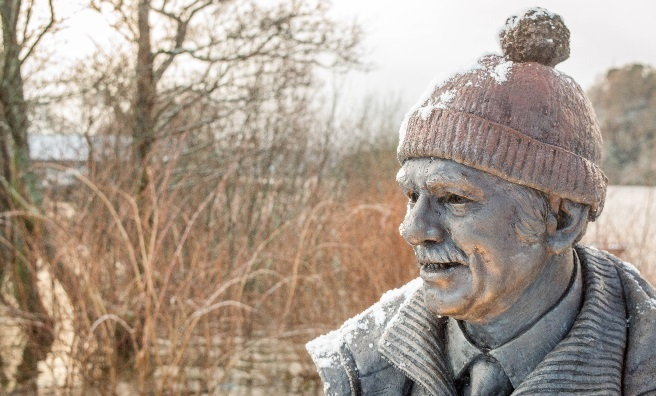 A snowy Tom Weir statue looks across Loch Lomond. Photo by Paul Saunders Photography